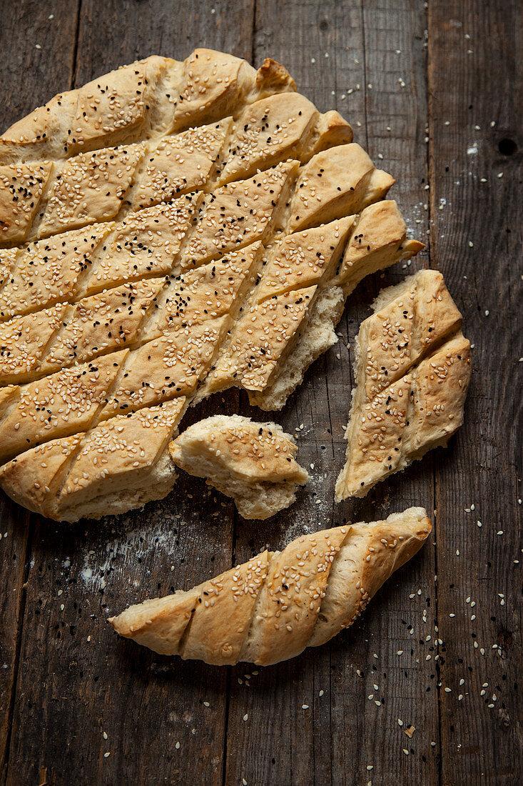 Unleavened bread with sesame seeds and black caraway, broken