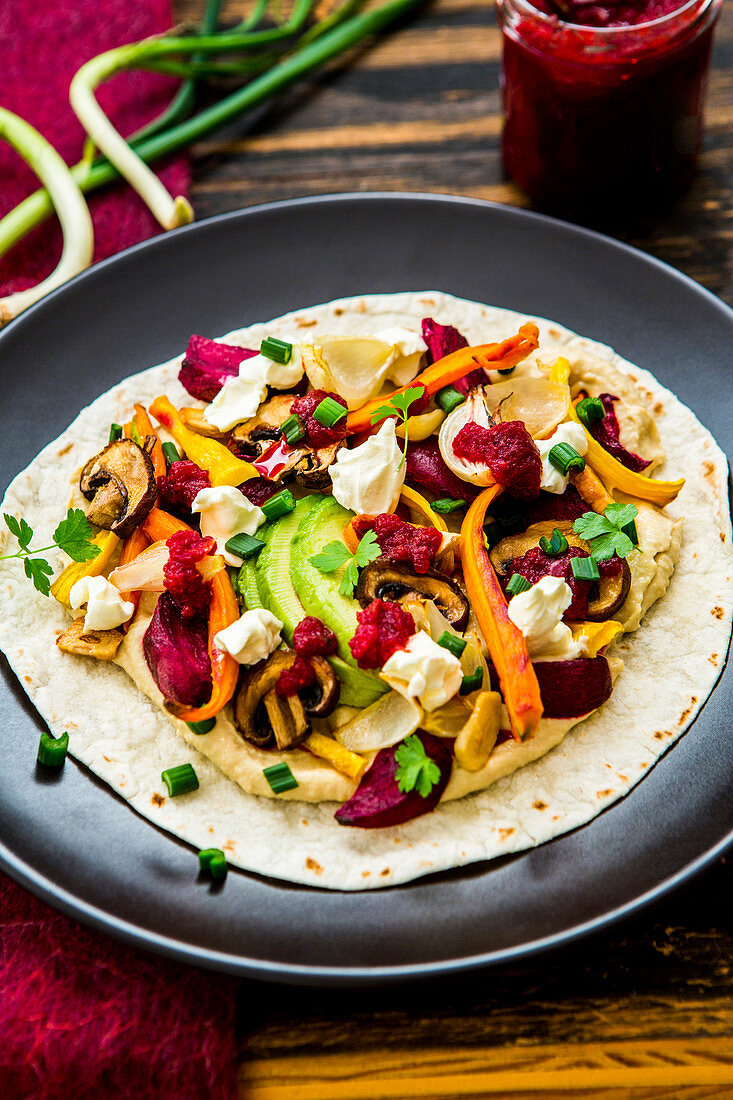 Tortilla with hummus, oven-roasted vegetables, avocado, crème fraîche and beetroot pesto