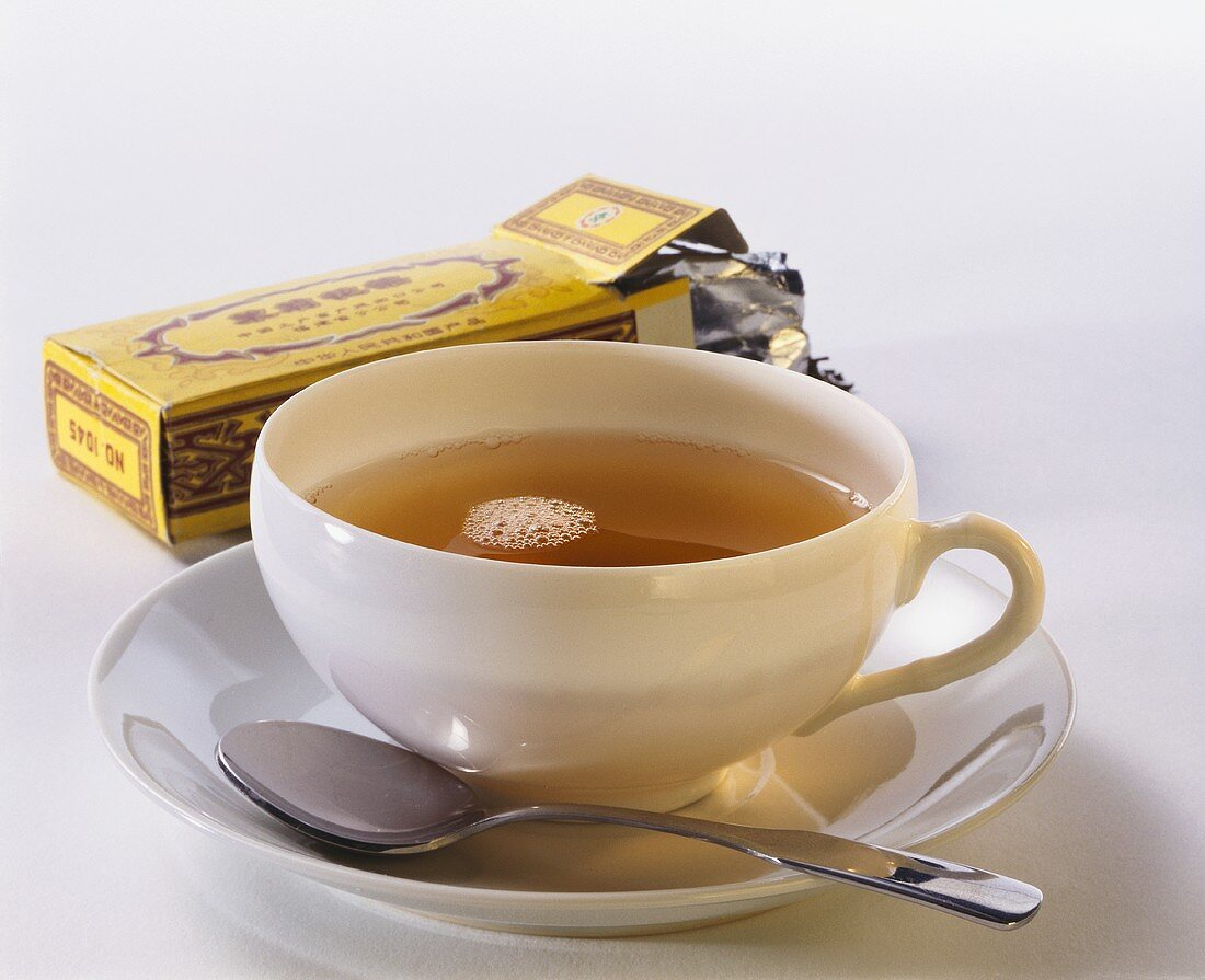 A cup of black tea and a tea packet from China