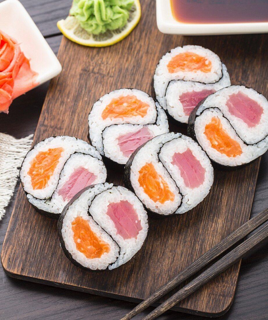 Yin yang futomaki with tuna and salmon on a wooden board