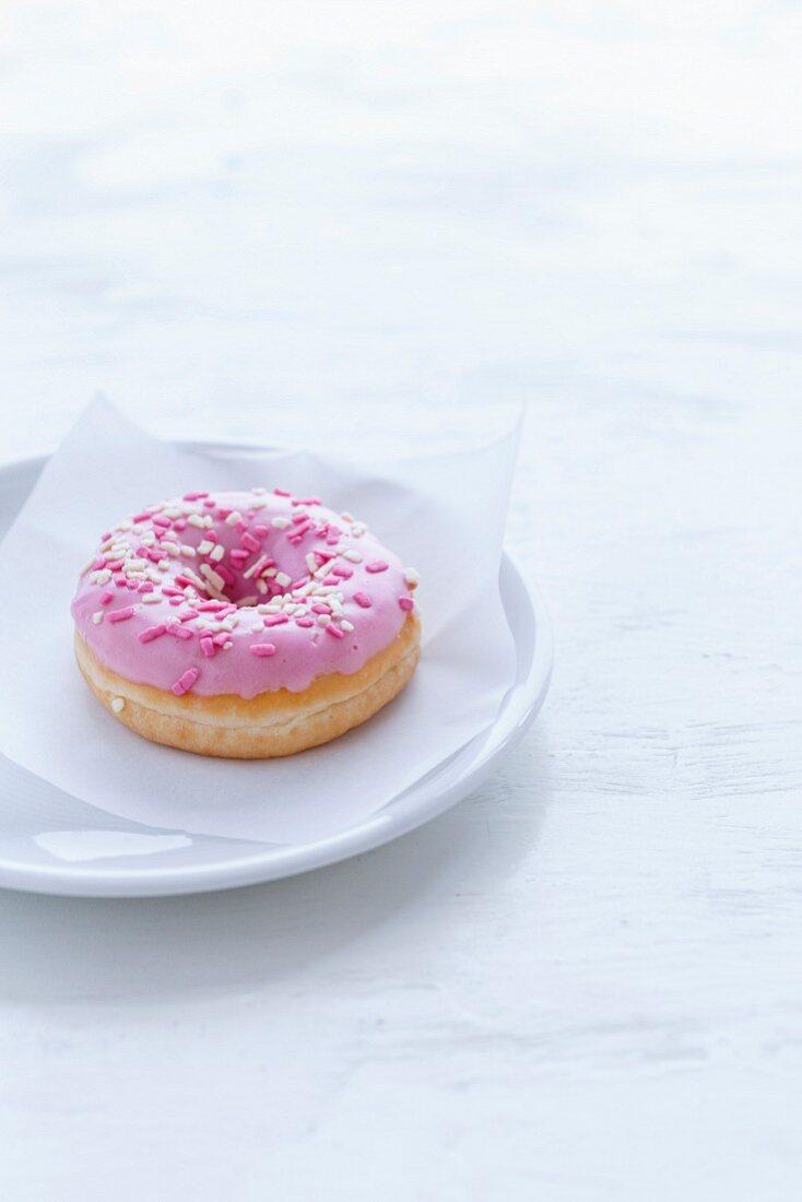 Doughnut mit rosa Zuckerglasur auf weißem Teller