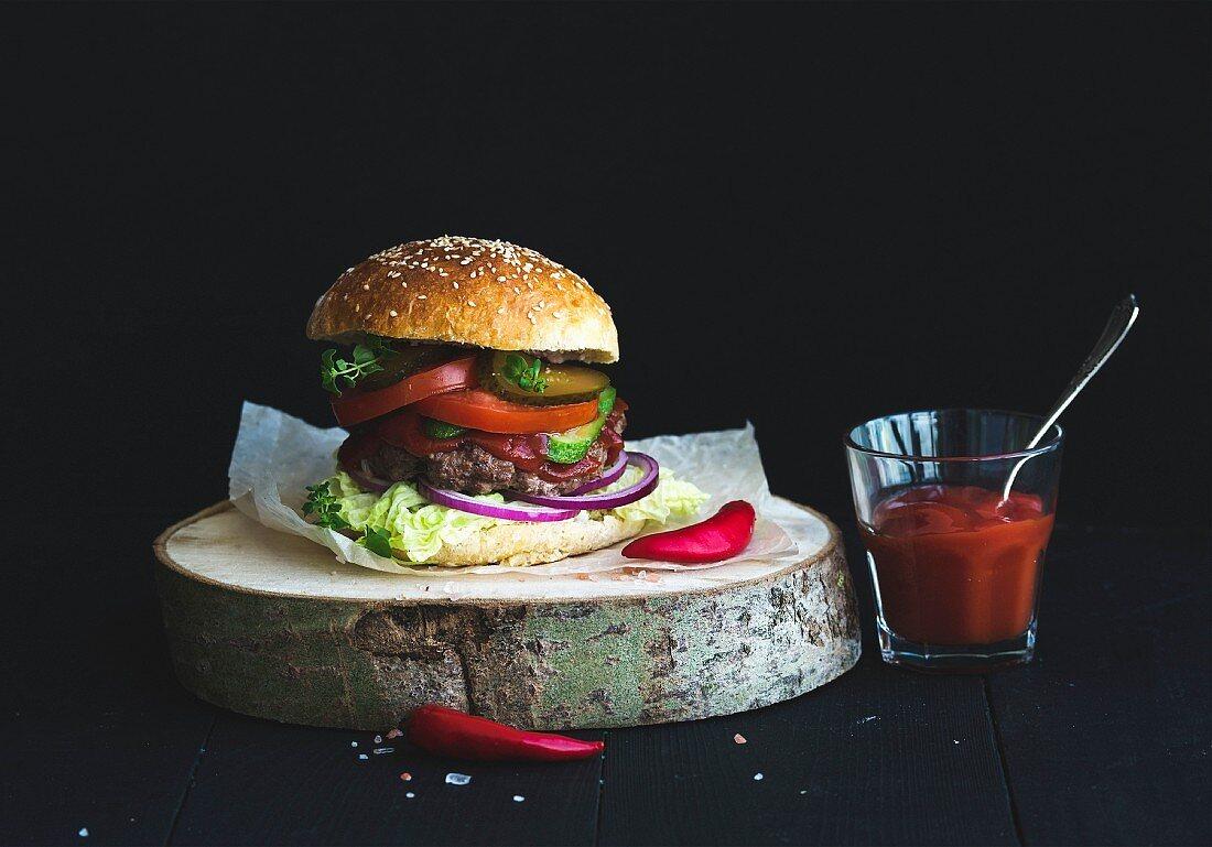Selbst gemachte Burger auf Holzscheibe, daneben scharfe Tomatensauce im Glas