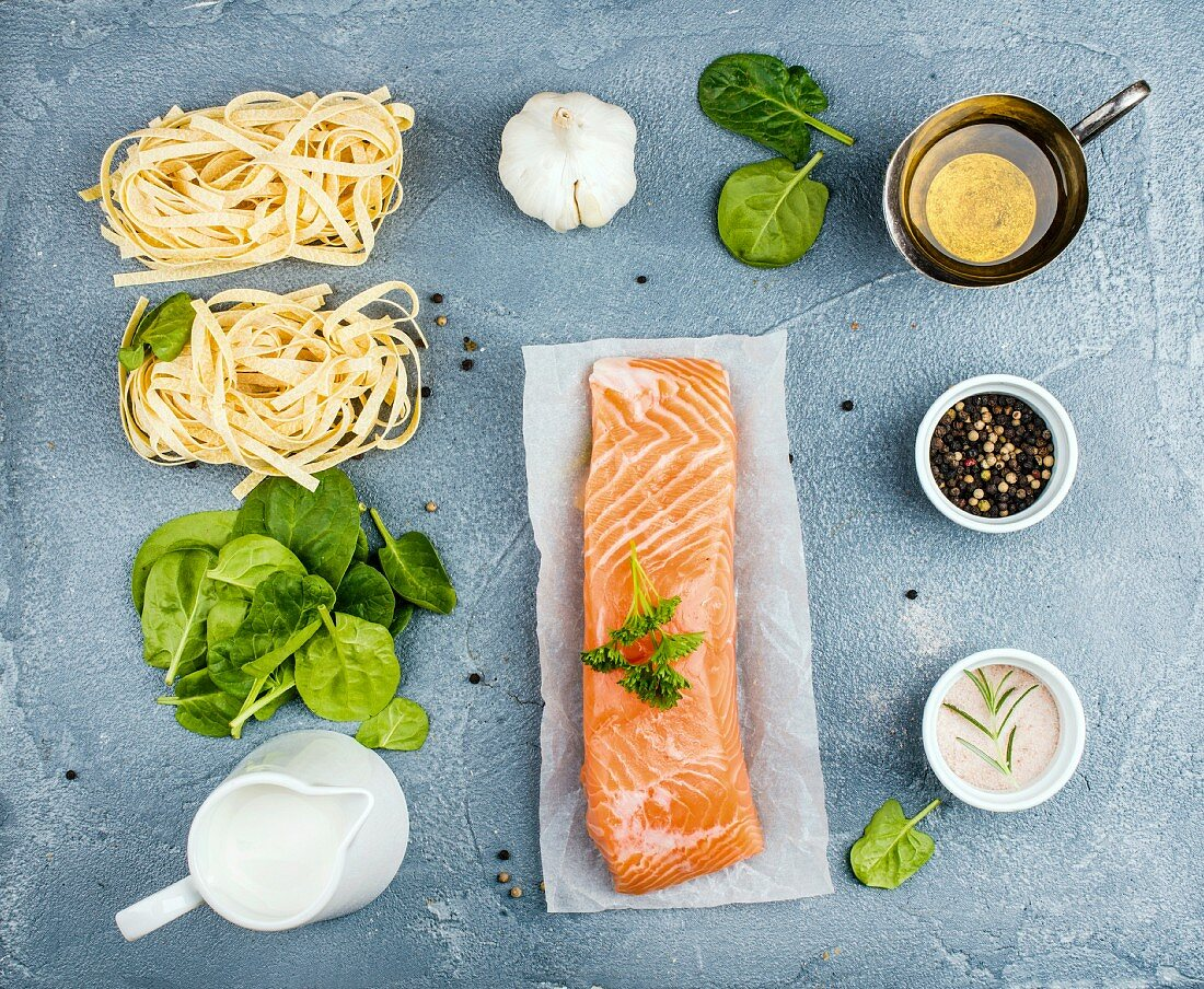 Ingredients for cooking pasta tagliatelle with salmon, spinach and cream on grey background