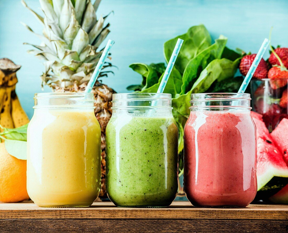 Freshly blended fruit smoothies of various colors and tastes in glass jars