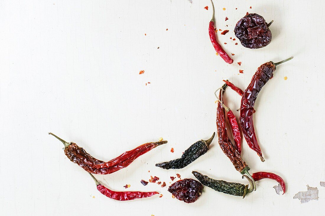 Assortment of dryed red hot chili peppers over white wooden background