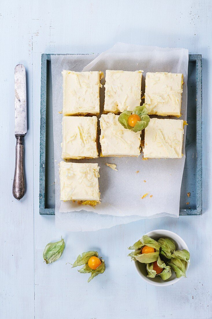 Homemade sliced cake with creamy mousse and tropical fruits mango and physalis served in wooden tray