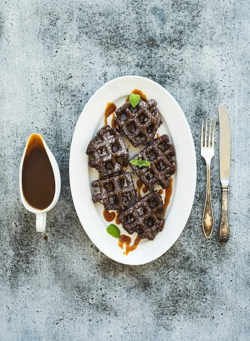 Chocolate Belgian waffles with salted caramel sauce and mint on white ceramic serving plate