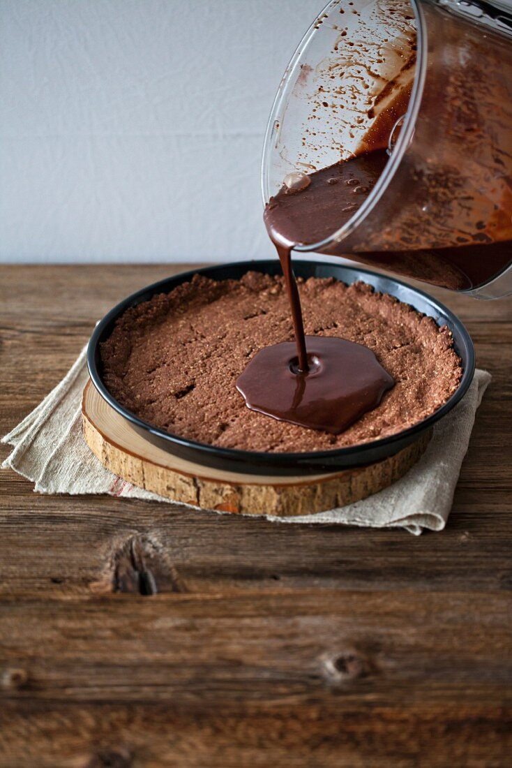 Pouring melted chocolate on the tart crust