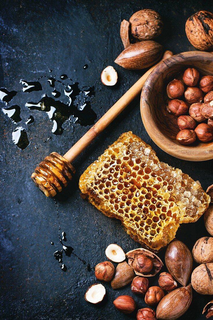 Honigwabe, Honiglöffel und verschiedene Nüssen auf altem Holztisch