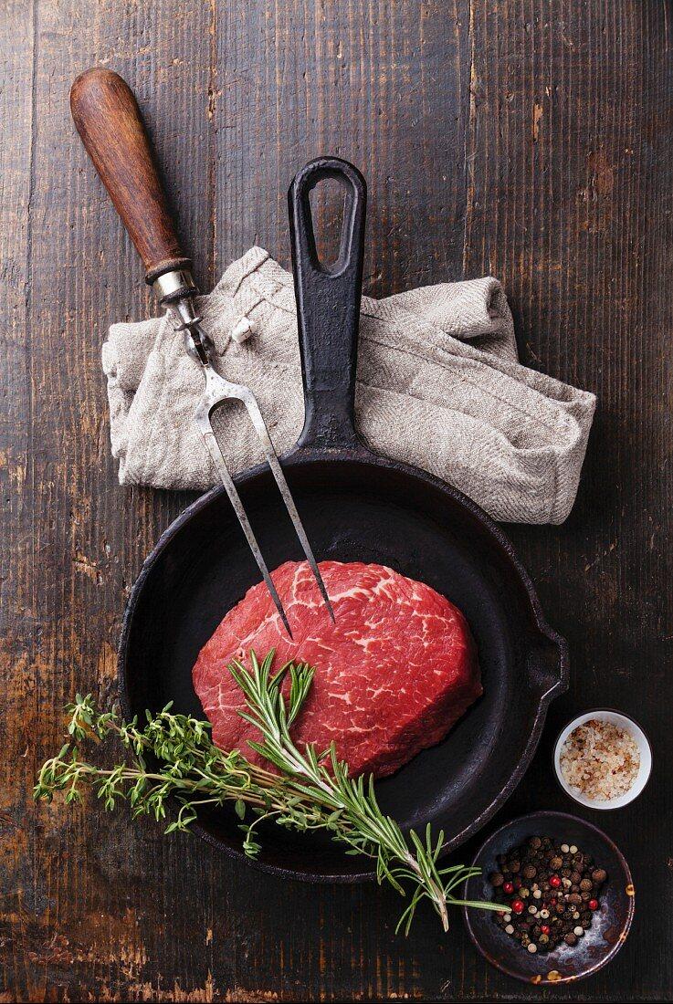 Rohes Ribeye-Steak mit Kräutern, in Gusseisenpfanne, Gewürze im Schälchen