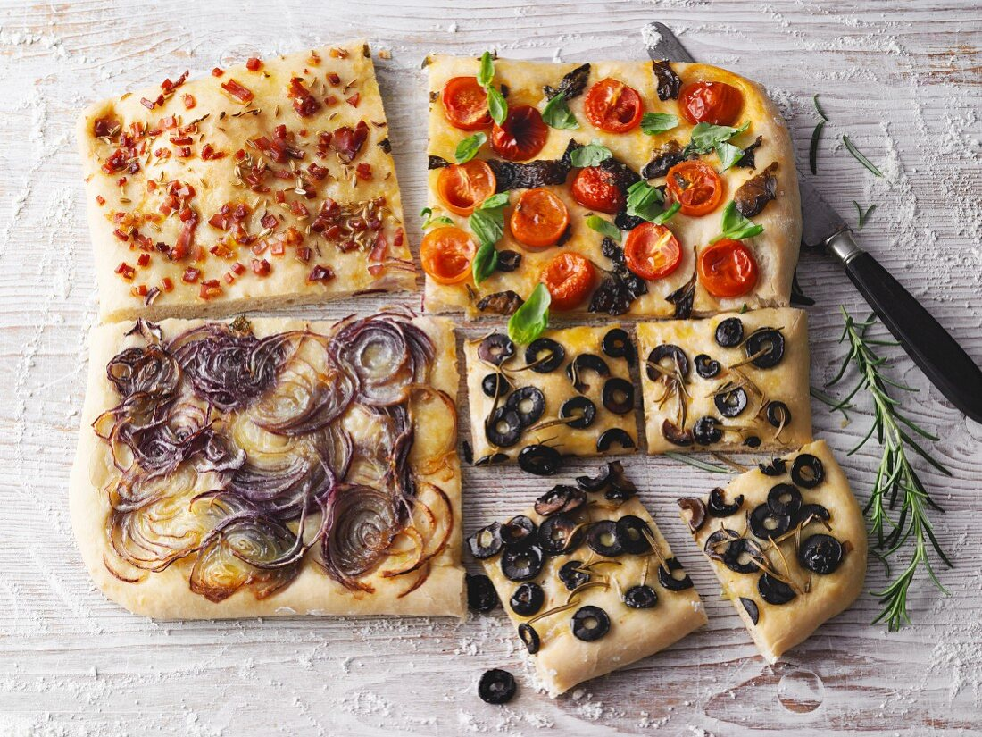 Four variations of focaccia with onion, olives, bacon and cherry tomatoes