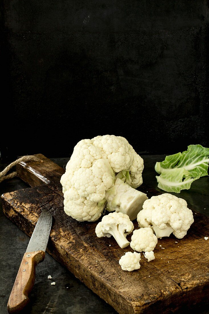 Cauliflower on a wooden board, partly divided into florets