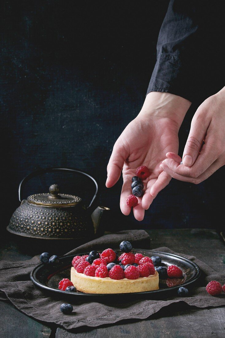 Female hands decorating by berries tart with custard, raspberries and blueberries