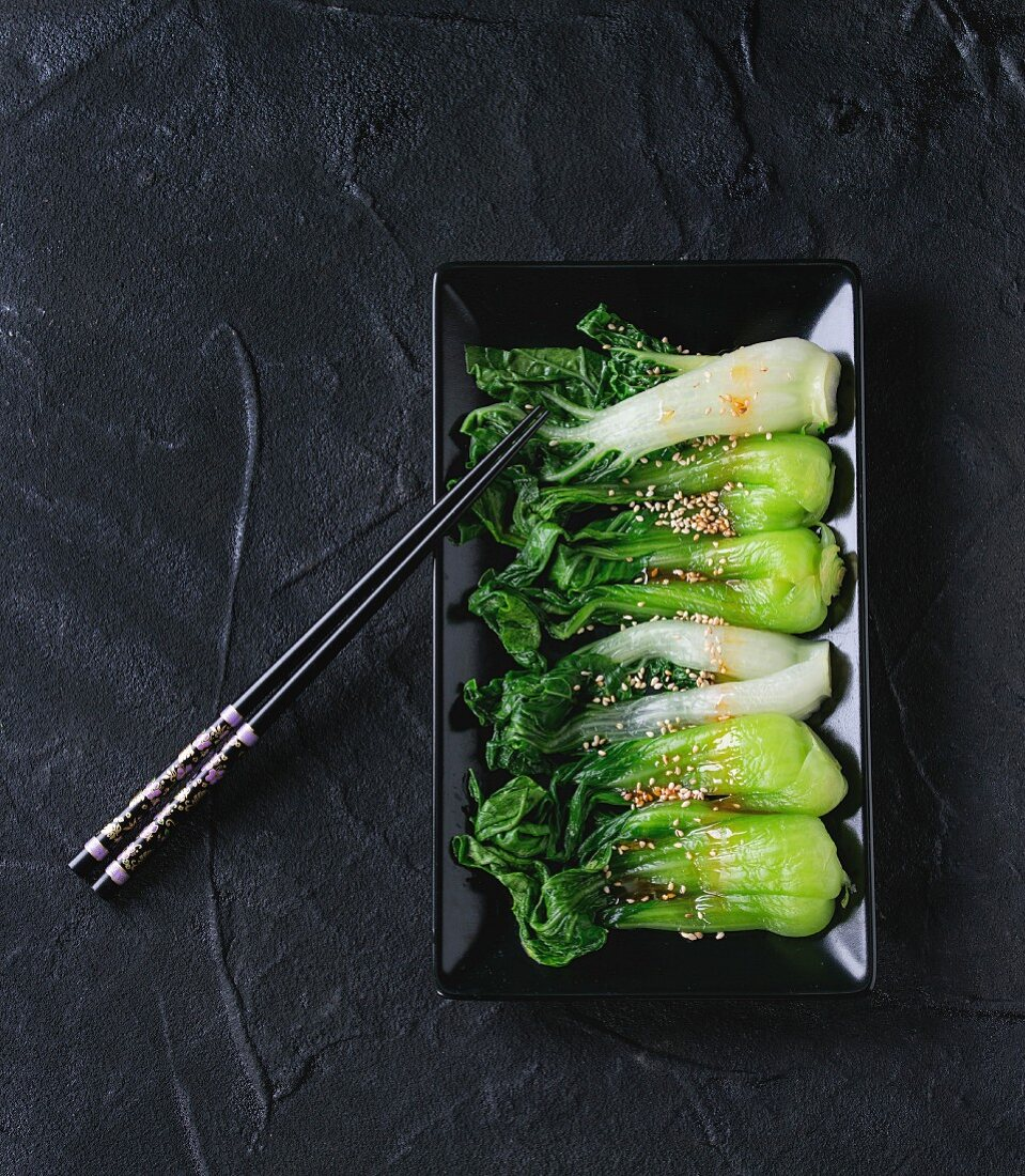 Cooked bok choy with sesame seeds and chili pepper olive oil in black square ceramic plate with black chopsticks