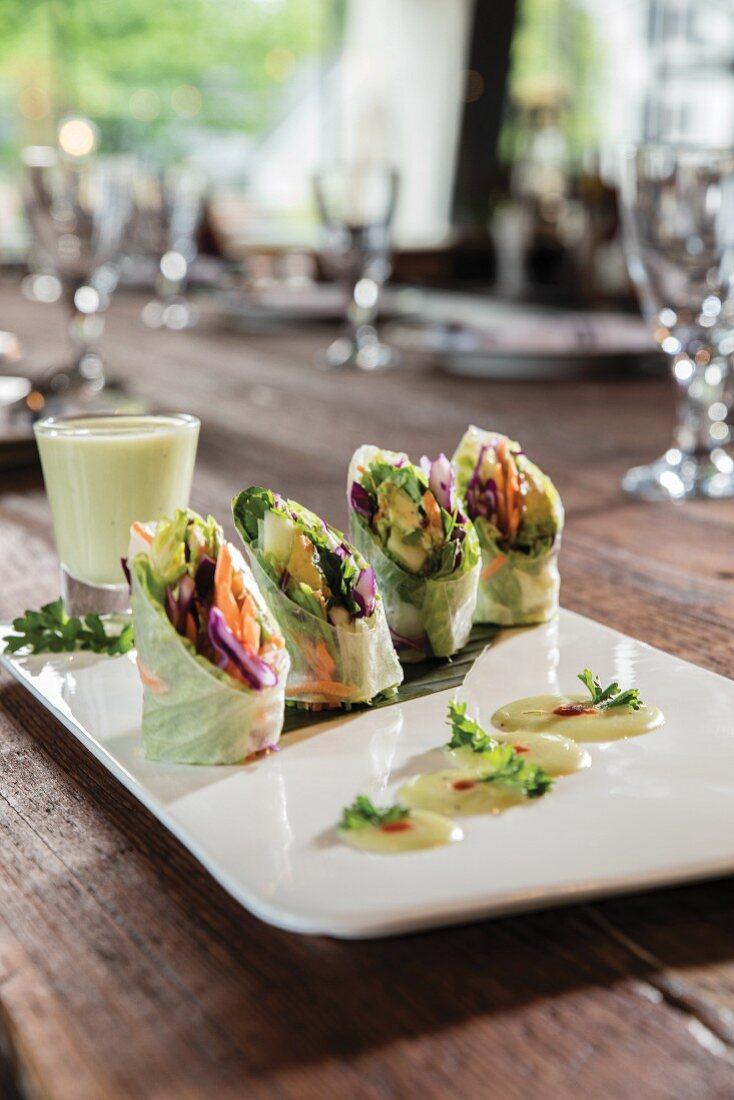 Four basil rolls with a shotglass ofhoney wasabi aioli