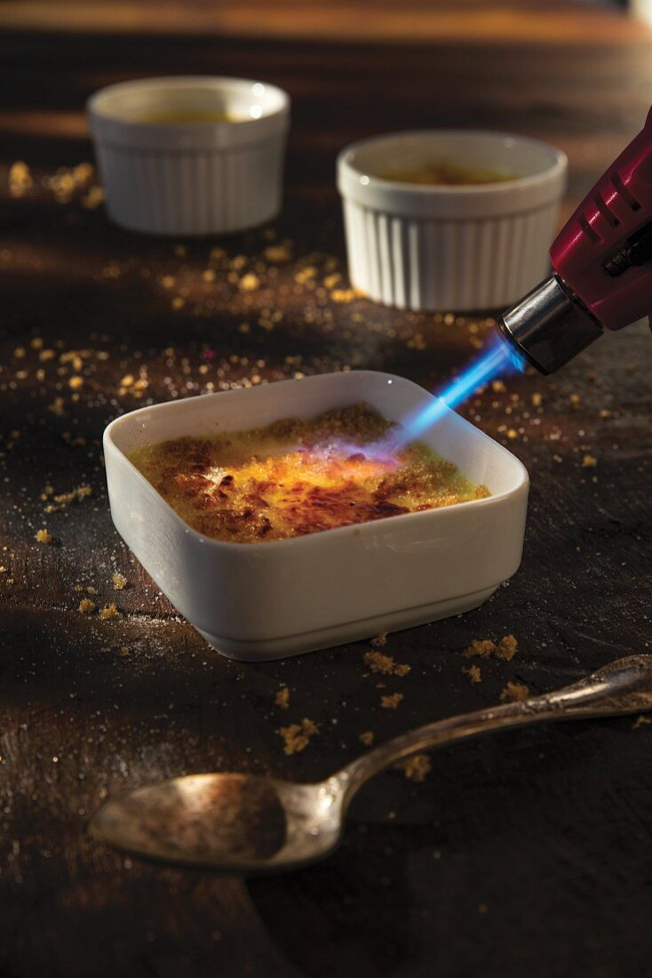 Coconut crème brûlée being caramelised with the flame of a gas burner