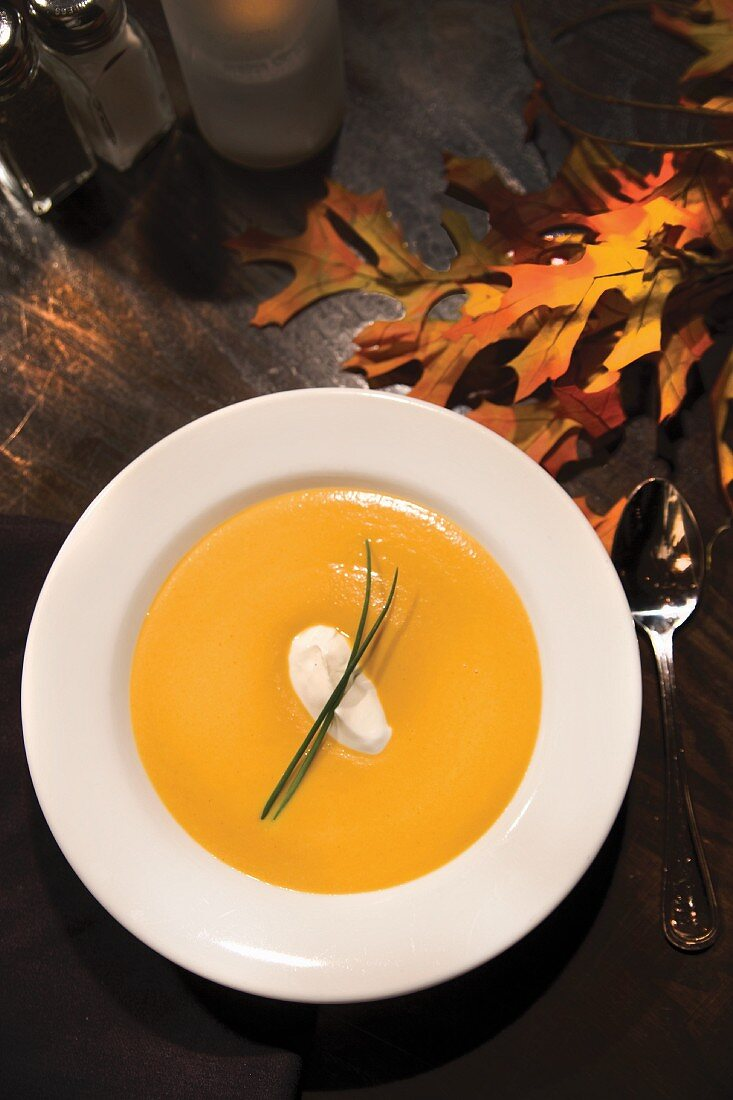 Ginger Yam Bisque in white bowl with autumn leaves