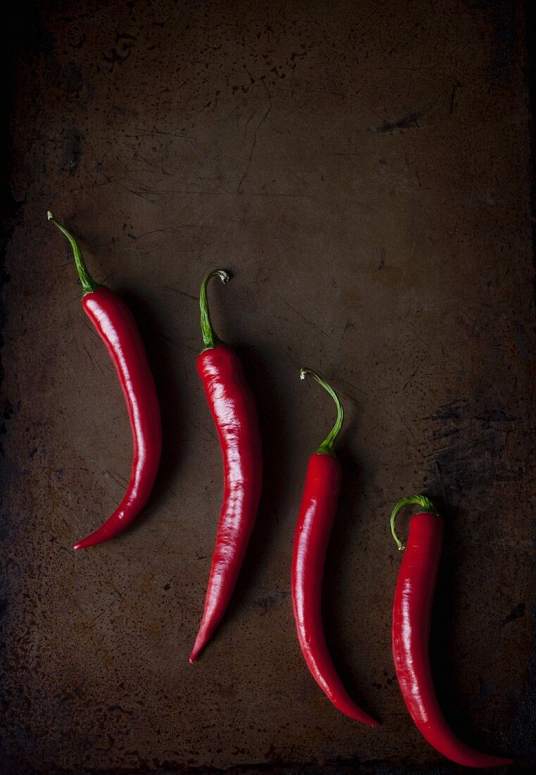 Four fresh red chillies on a metal tray