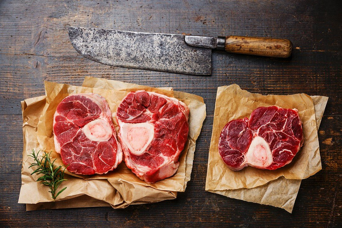 Raw fresh cross cut veal shank for making Osso Buco on wooden background with meat cleaver