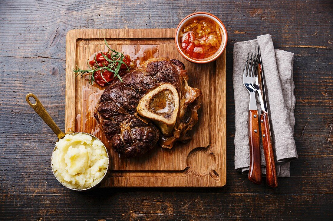 Prepared Osso buco Veal shank with tomatoes and mashed potatoes on serving board on wooden background
