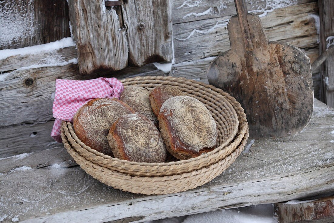Several wood oven baked breads in a basket on a wooden bench in front of a mountain hut