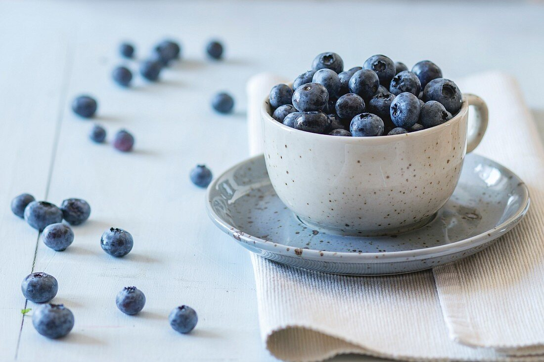 Spotted blue ceramic cup of blueberries with saucer at white textile napkin over wooden table