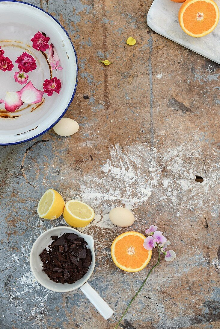 Chocolate, lemon, orange, eggs and a bowl of water with floating flowers on a vintage background