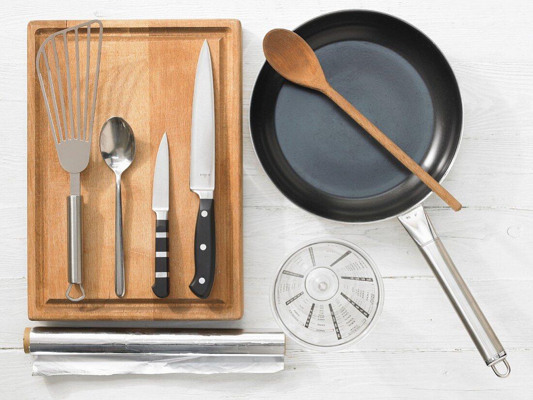Various kitchen utensils: pan, spatula, knife, measuring cup, aluminium foil