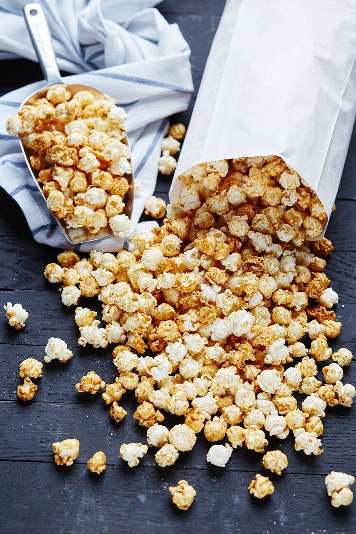 Paper bag and metal scoop full of popcorn on black background