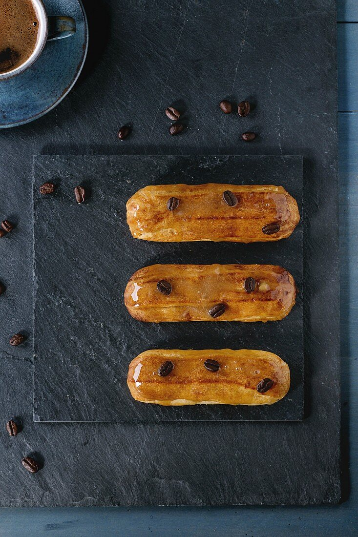 Coffe eclairs with cup of fresh black coffee and coffee beans on black slate board over blue wooden surface