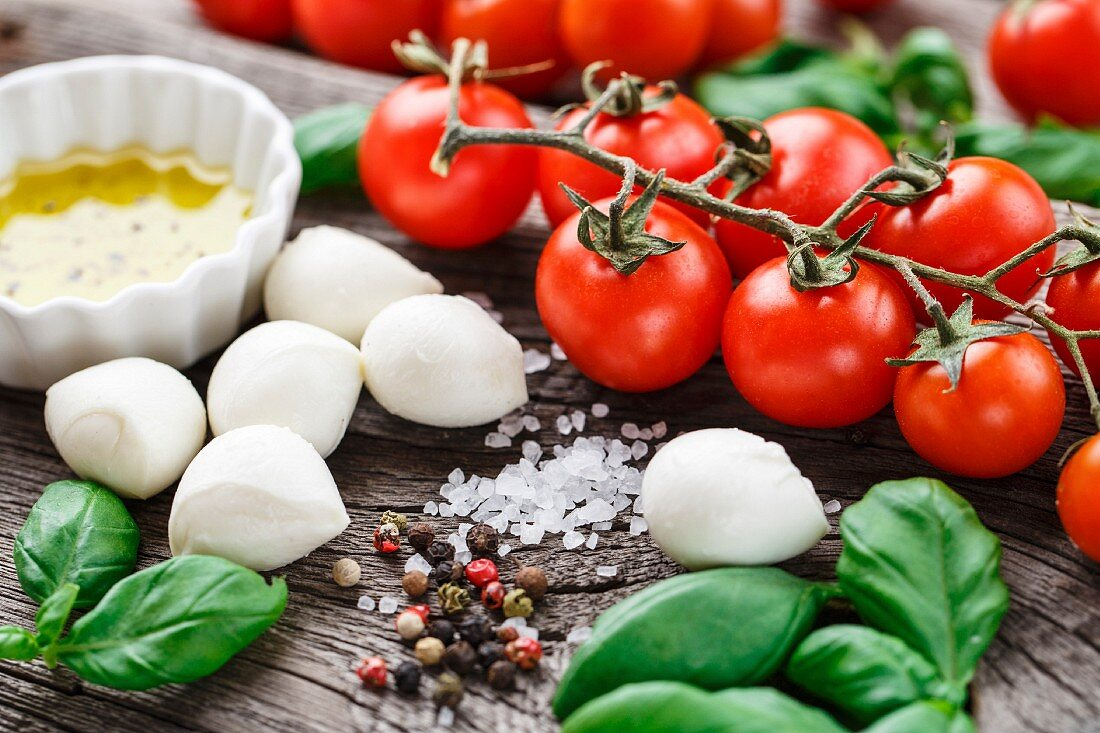 Cherry tomatoes, basil leaves, mozzarella cheese and olive oil for caprese salad