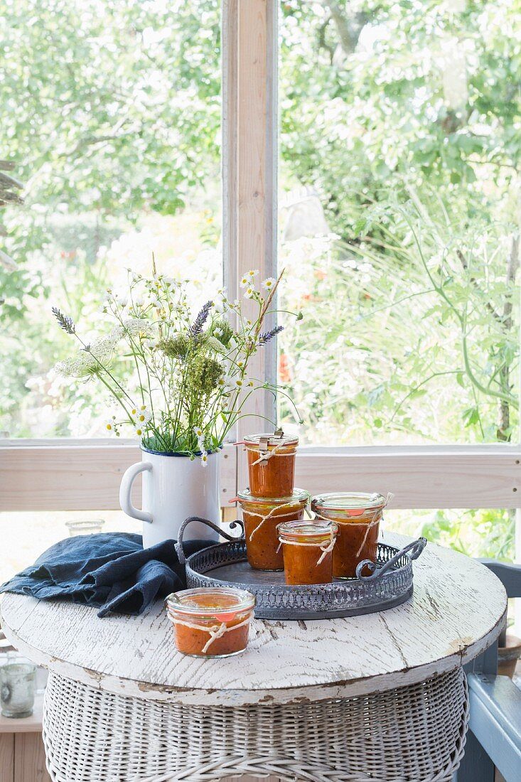 Apricot chutney jars on vintage tray, with grey kitchen towel and flower bouquet on white wooden table