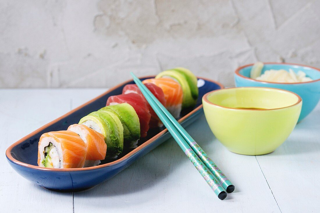 Sushi set salmon and avocado rolls served in bright ceramic plates with chopsticks and soy sauce on blue wooden table