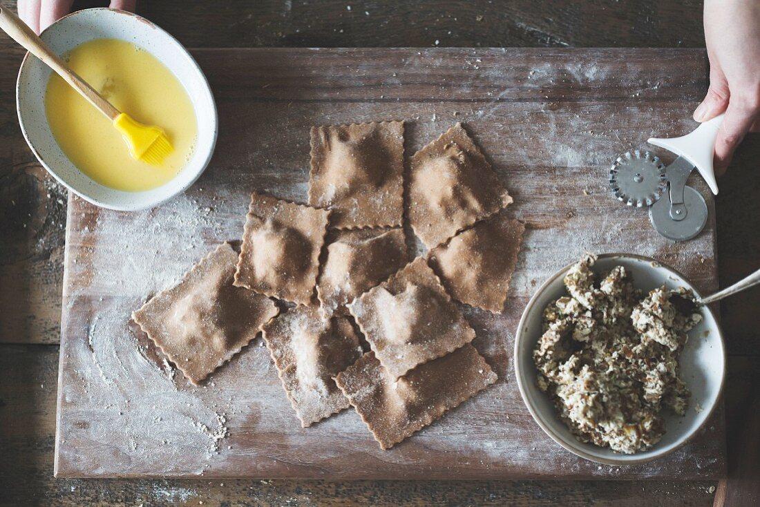 The cooking of chestnut flour ravioli with artichokes, peas and enoki mushrooms