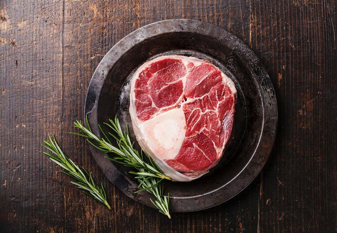 Raw fresh cross cut veal shank for making Osso Buco and rosemary on metal plate dark wooden background
