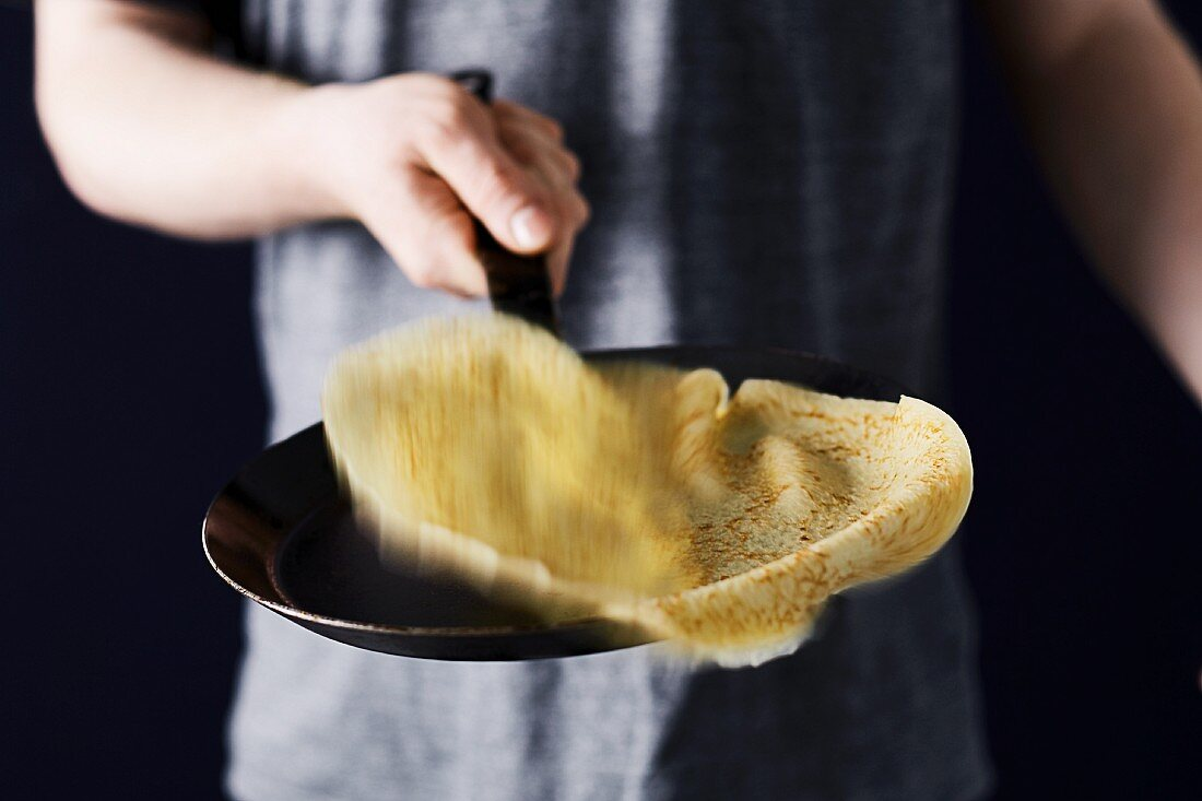 A pancake being tossed in the pan