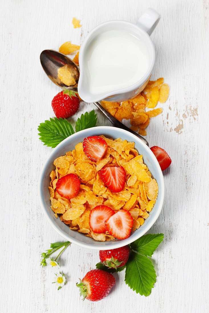 Healthy Breakfast with corn flakes, milk and strawberry on old wooden background