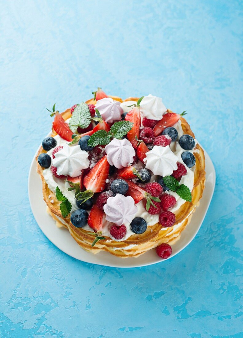 Waffle cake with berries and meringue rosettes