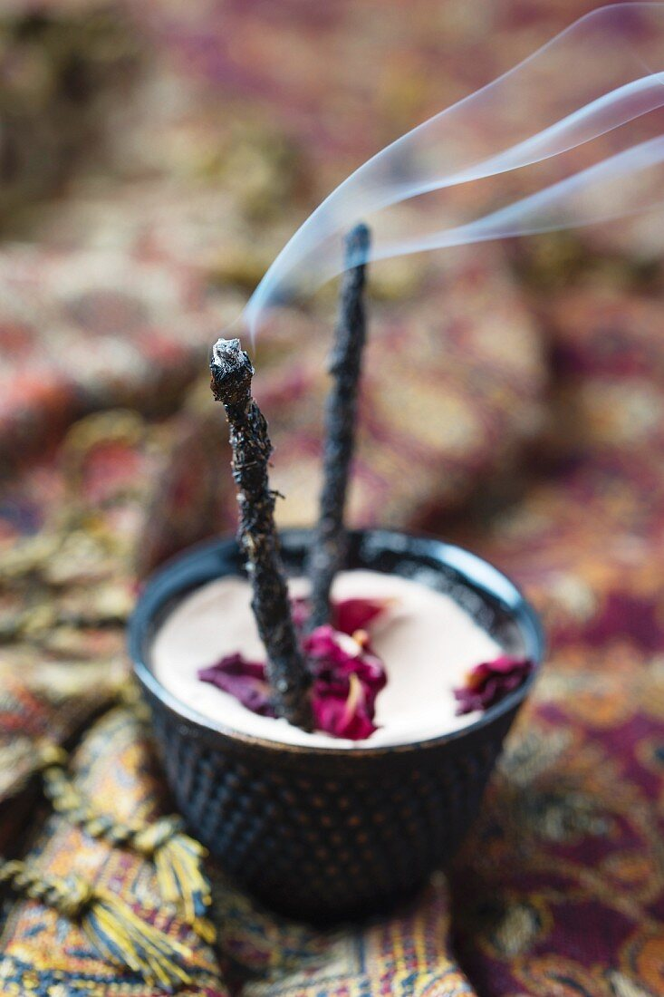 Homemade incense sticks with smoked coal, resin, dried herbs and flowers
