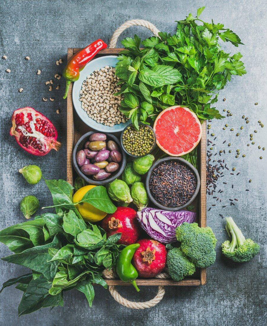 Superfood-Stillleben mit Gemüse, Obst, Samen, Getreide, Bohnen, Gewürzen und Kräutern in Holzkiste