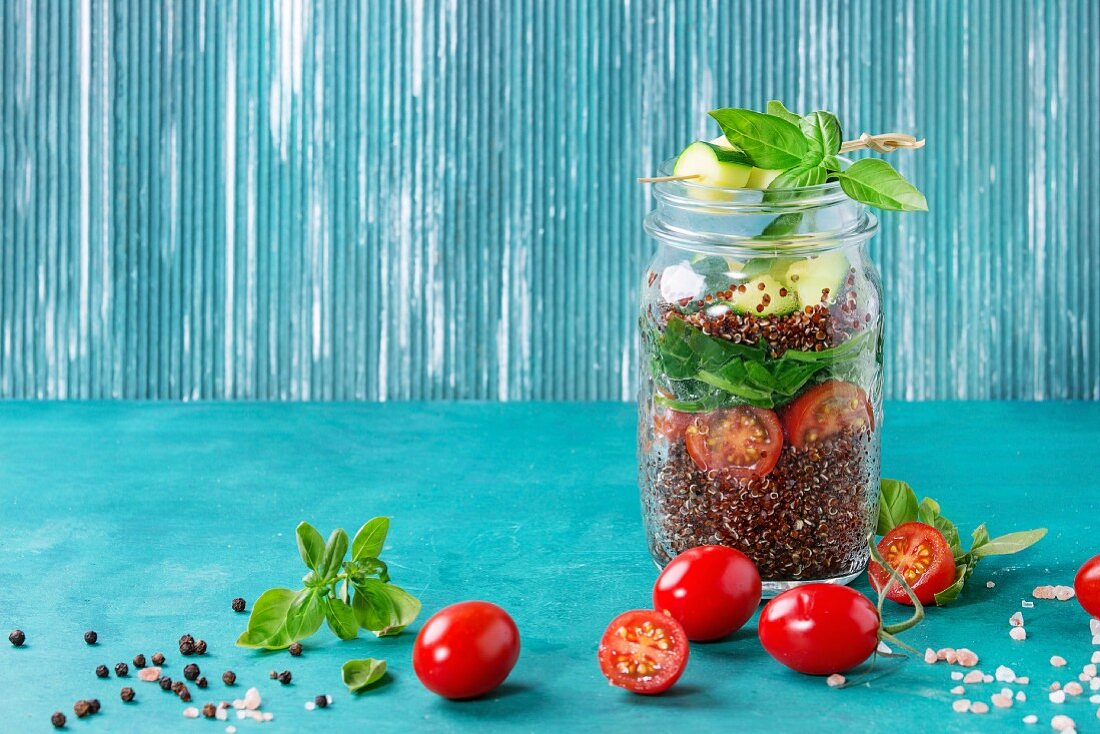 Salad with quinoa, spinach, tomatoes and zucchini in glass mason jars