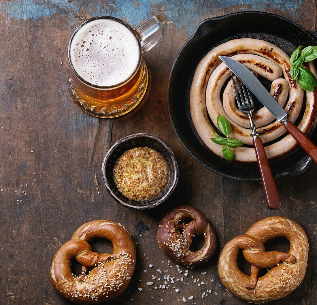 Glass of lager beer with fried sausage in pan with cutlery and traditional salted pretzels and bowl of mustard