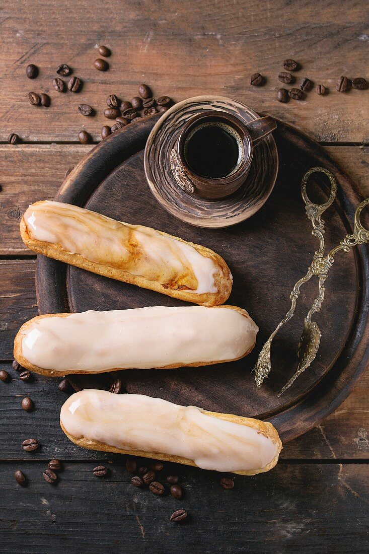 Fresh homemade eclairs with different glaze, coffee beans and ceramic cup of black coffee over wooden background