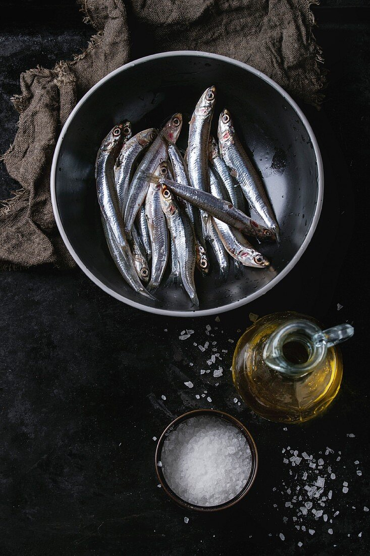 Lot of raw fresh anchovies fishes in black ceramic bowl with sea salt and bottle of olive oil for marinade