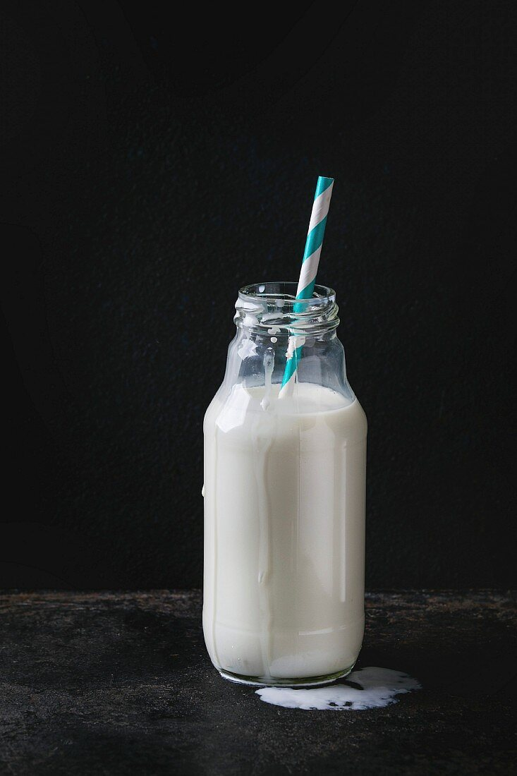 Opened glass bottle full of milk with spot of milk and striped retro cocktail tube over black background