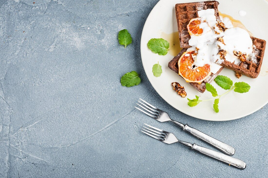 Belgian soft waffles with blood orange, cream, marple syrup and mint on white plates over concrete textured background