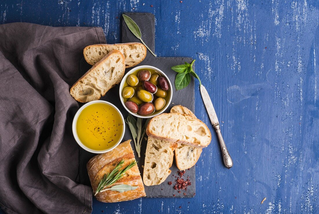 Olives, oil, herbs and sliced ciabatta bread on black slate stone board over painted dark blue background