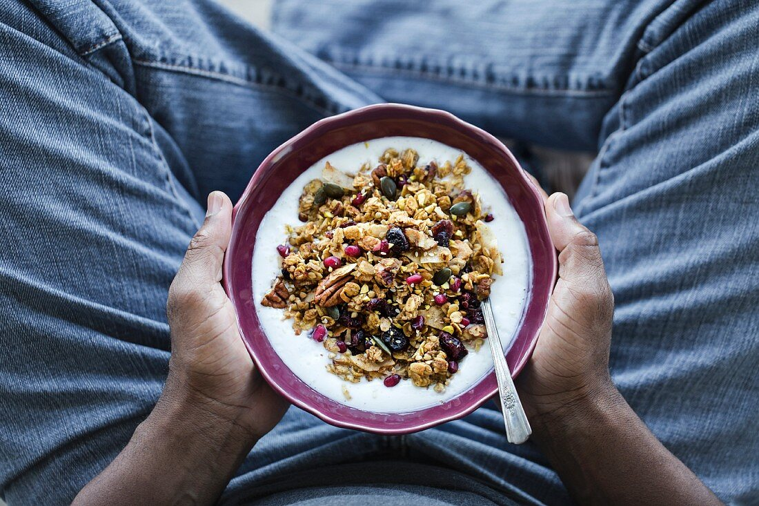 A bowl of Spicy Pumpkin Granola is in the hands of a man
