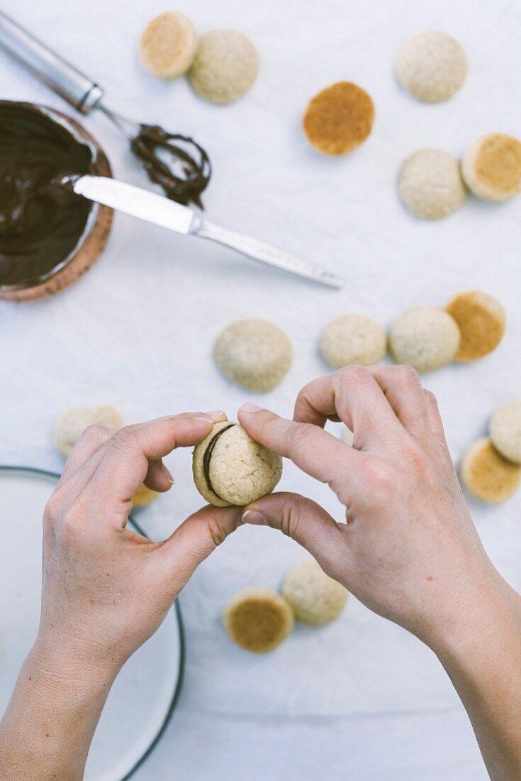 Hände beim Zusammensetzen von Sandwich-Cookies mit Schokolade