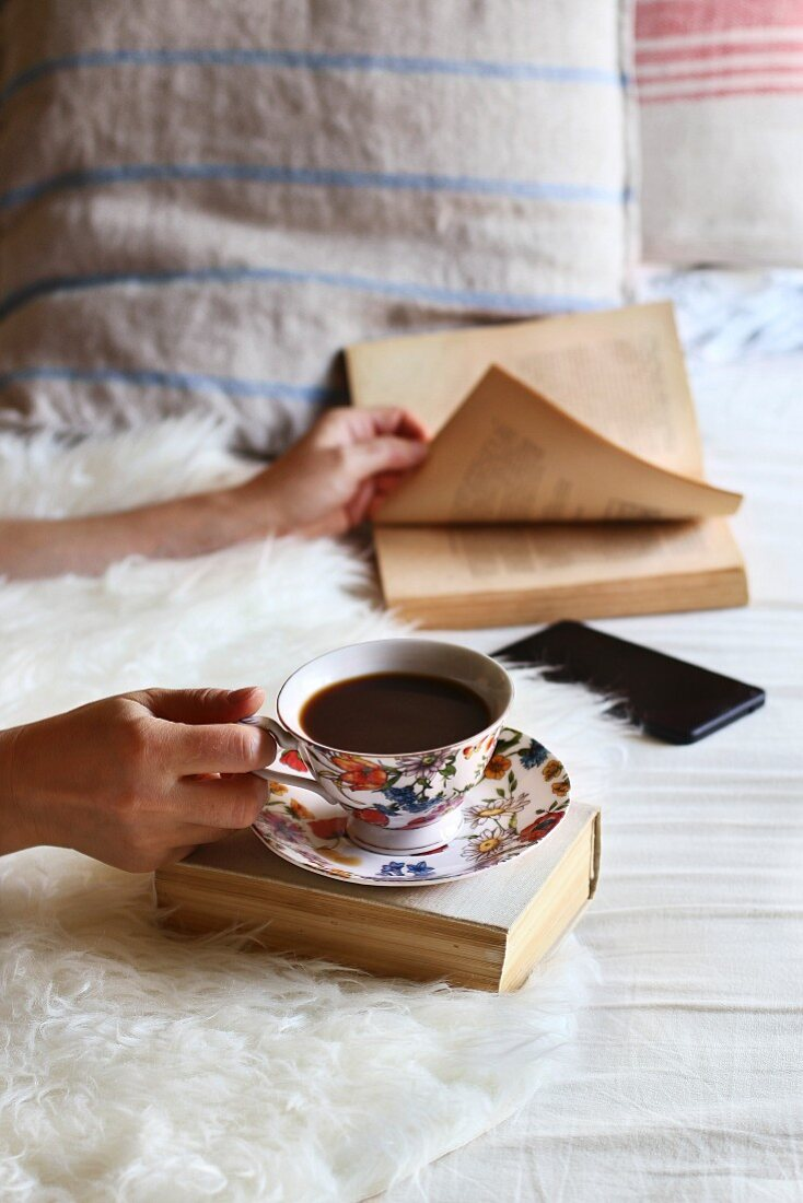 Female sitting on the bed, leafing through a book and drinking a cup of coffee